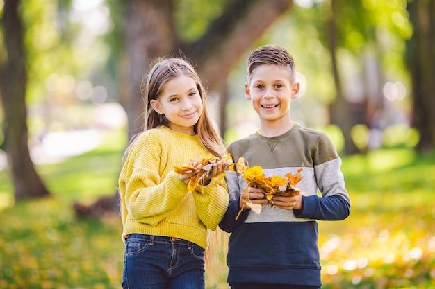 Heureux frères et sœurs caucasiens profitant de la journée d'automne dans le parc