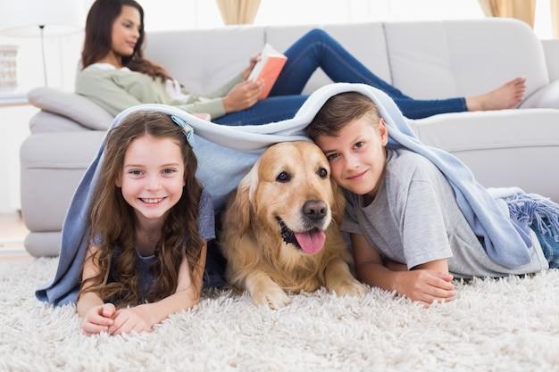 Heureux frères et sœurs avec chien sous couverture