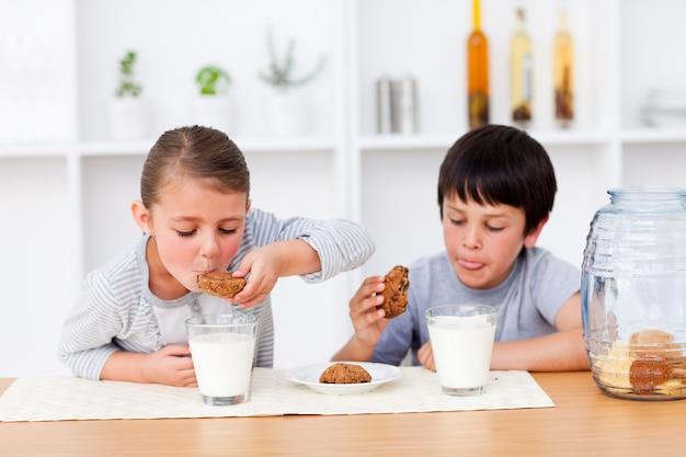 Heureux frères et sœurs mangeant des biscuits et buvant du lait