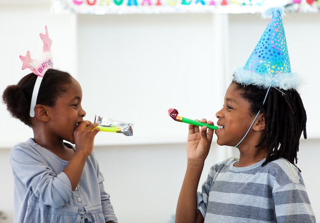 Heureux frères et sœurs s'amuser lors d'une fête d'anniversaire