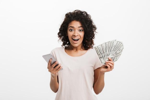 Heureux gagnant femme américaine avec coiffure afro et grand sourire tenant le prix de l'argent dollar en espèces et smartphone en argent, isolé sur mur blanc