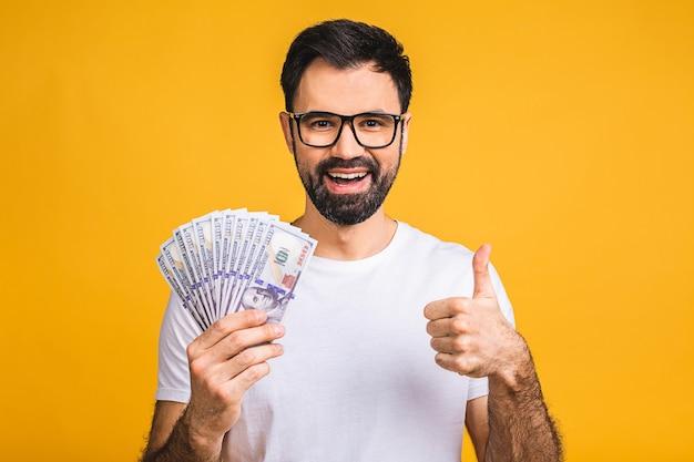 Heureux gagnant! jeune homme riche en argent détenant des billets d'un dollar avec surprise isolé sur fond jaune.