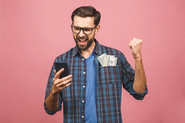 Heureux gagnant! jeune homme riche en chemise à carreaux tenant des billets d'un dollar en argent dans la poche avec surprise isolé sur fond rose. utilisation du téléphone.