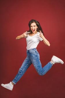 Heureux gagnant. portrait de toute la longueur d'une joyeuse jeune femme caucasienne célébrant le succès tout en sautant isolé sur fond rouge.