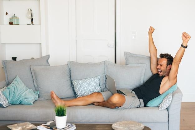 Heureux gai jeune homme blond assis dans le canapé à la maison en regardant le football