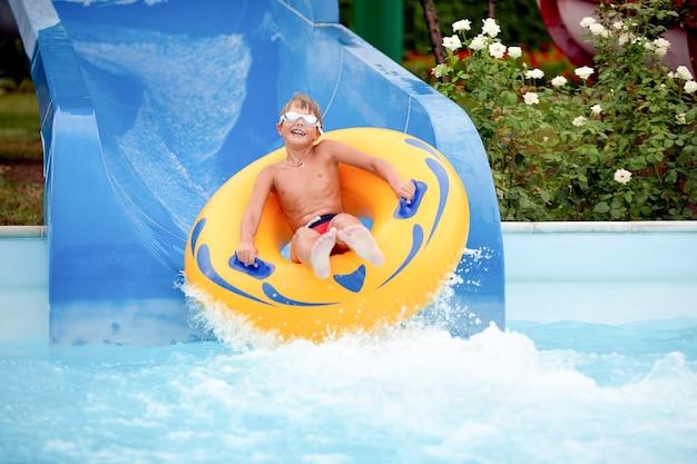 Heureux un garçon de 8 ans monte dans le parc aquatique sur des cercles gonflables sur des toboggans avec éclaboussures