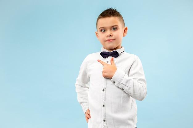 Heureux garçon adolescent souriant isolé sur fond bleu studio. beau portrait mâle demi-longueur. jeune enfant émotionnel pointant vers la gauche. le