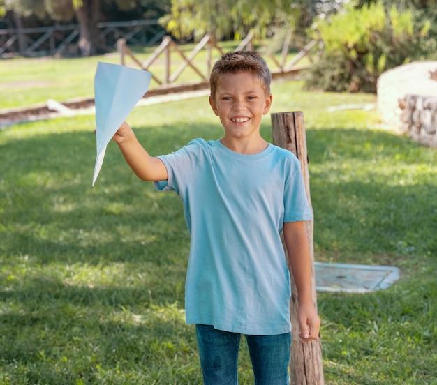 Heureux garçon d'âge préscolaire joue avec un avion en papier dans un parc