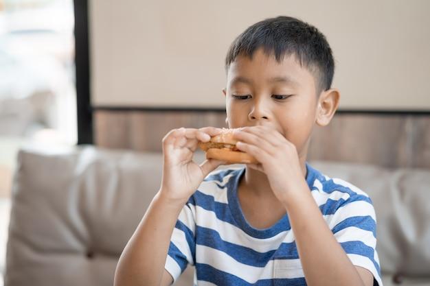 Heureux garçon asiatique manger un hamburger au restaurant