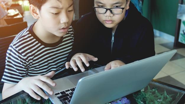 Heureux garçon asiatique taper sur un ordinateur portable.