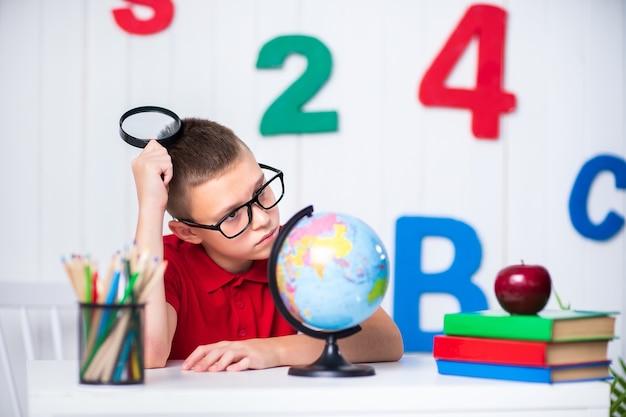 Heureux garçon assis au bureau avec globe, pomme et livres