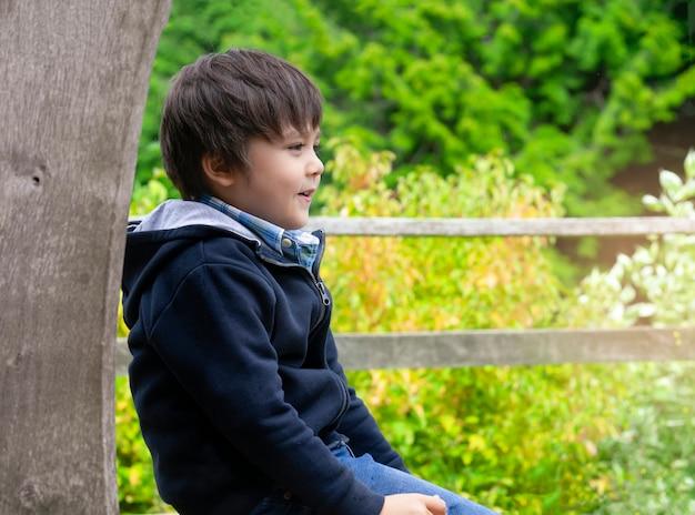 Heureux garçon assis sur un banc en bois avec un visage souriant dans le parc
