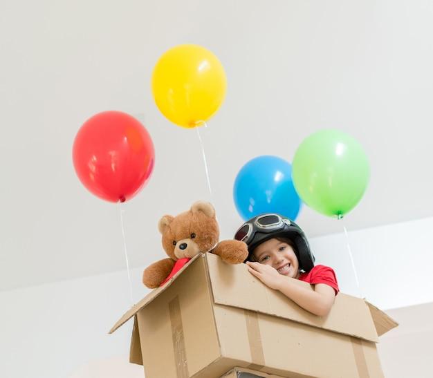 Heureux garçon assis dans sa boîte en imaginant voler lui-même