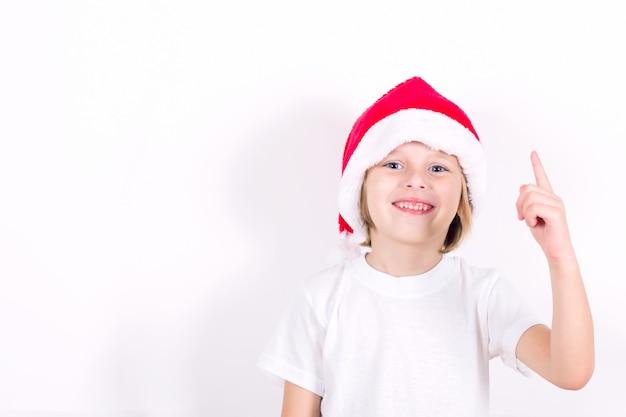 Heureux garçon au chapeau rouge santa pointant avec son doigt. concept pour noël