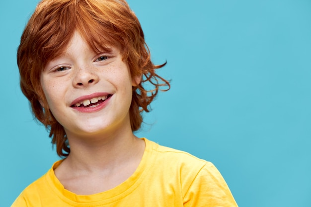 Heureux garçon aux cheveux roux et avec des taches de rousseur sur son visage beau modèle souriant