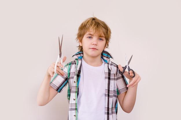 Heureux garçon blond apparence européenne dans une chemise blanche tenant des ciseaux
