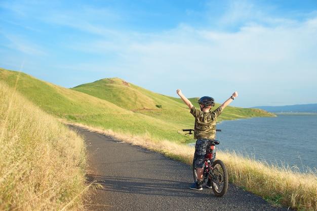 Heureux garçon à bras ouverts sur son vélo de montagne