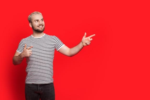 Heureux garçon caucasien aux cheveux blonds et à la barbe présente quelque chose près de lui pointant vers l'espace libre rouge