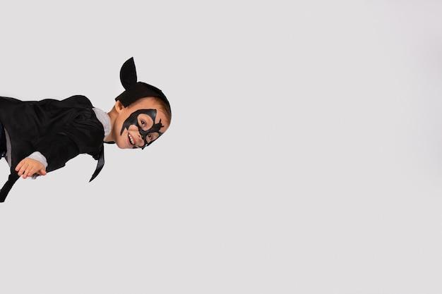 Heureux garçon en costume de chauve-souris noire avec des oreilles volant comme un éclair dans le ciel. .