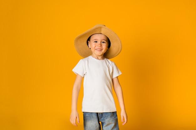 Heureux garçon dans un chapeau de paille sur une surface jaune avec un espace pour le texte