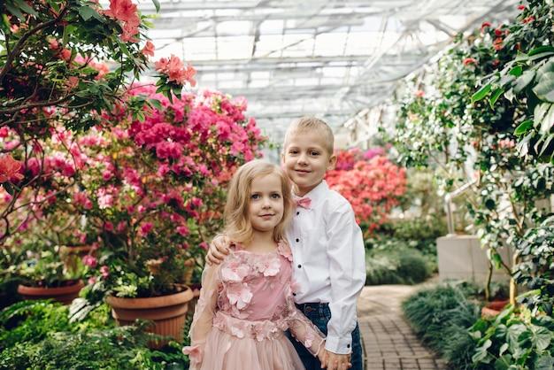 Heureux garçon et fille marchent étreignant dans le jardin fleuri de printemps