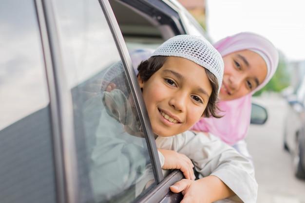 Heureux garçon et fille musulmans agitant à l'extérieur de la fenêtre de la voiture
