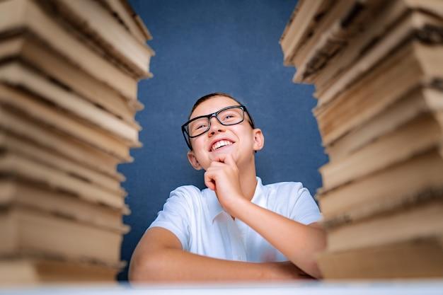 Heureux garçon intelligent dans des verres assis entre deux piles de livres et regarde en souriant.