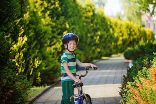 Heureux garçon jouant avec un bouquet de ballons à l'extérieur et sur un scooter.