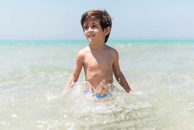 Heureux garçon jouant dans l'eau au bord de la mer