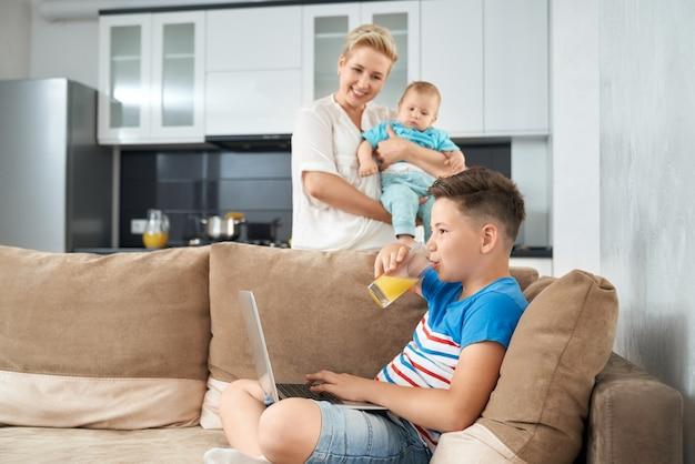 Heureux garçon jouant sur un ordinateur portable pendant que la mère tient enfant en bas âge