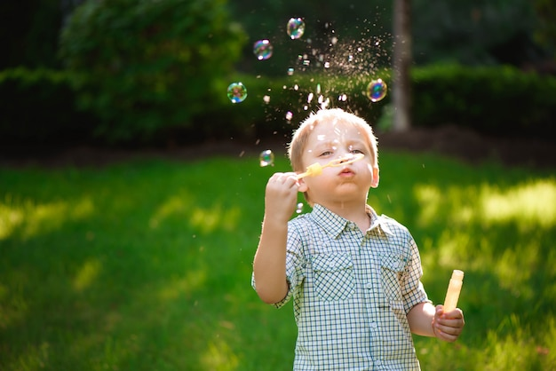 Heureux garçon joue dans des bulles à l'extérieur en été