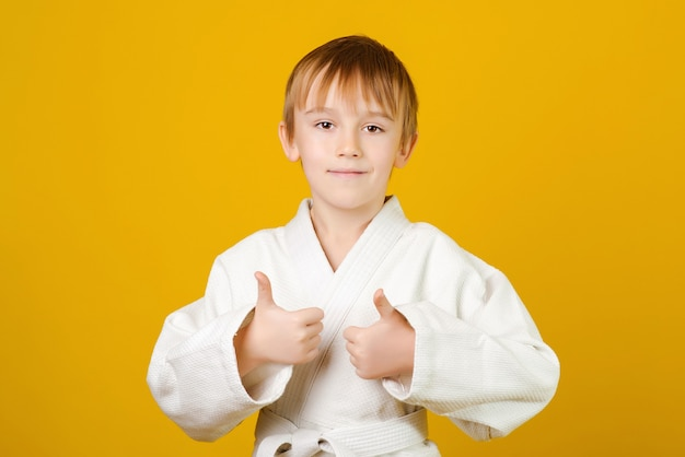Heureux garçon en kimono blanc pratique le judo.