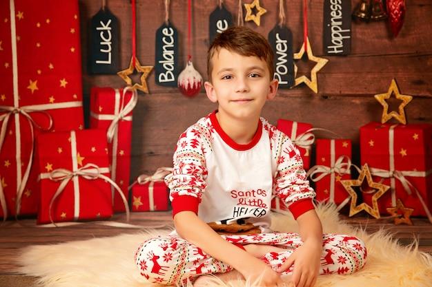 Heureux garçon mignon 10 ans sur le sol en pyjama en attente de la nouvelle année et joyeux noël, enfance et famille