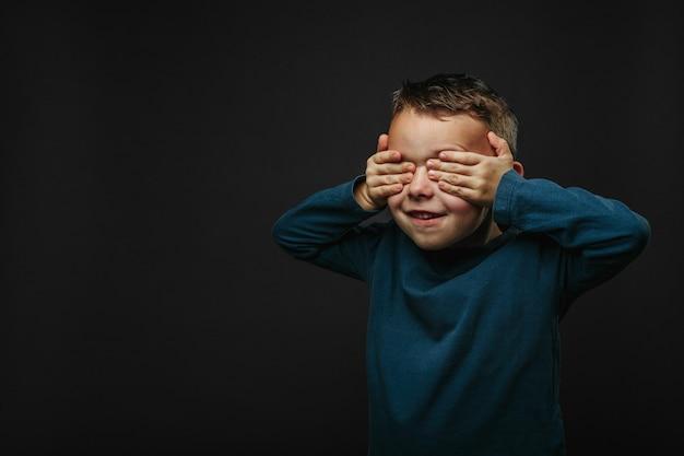 Heureux garçon mignon s'amuse joué sur le mur de fond noir en attente d'une surprise photo lumineuse d'un garçon