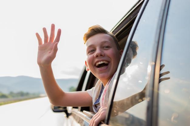 Heureux garçon musulman agitant la fenêtre de la voiture à l'extérieur