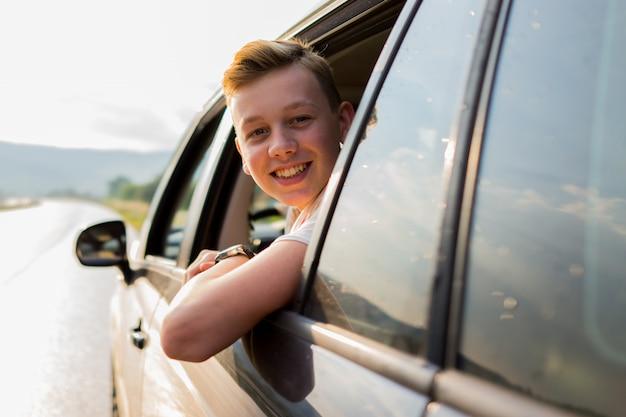 Heureux garçon musulman regardant à l'extérieur de la fenêtre de la voiture