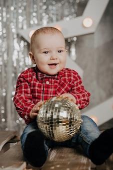 Heureux garçon nouveau-né souriant assis sur un décor de fond