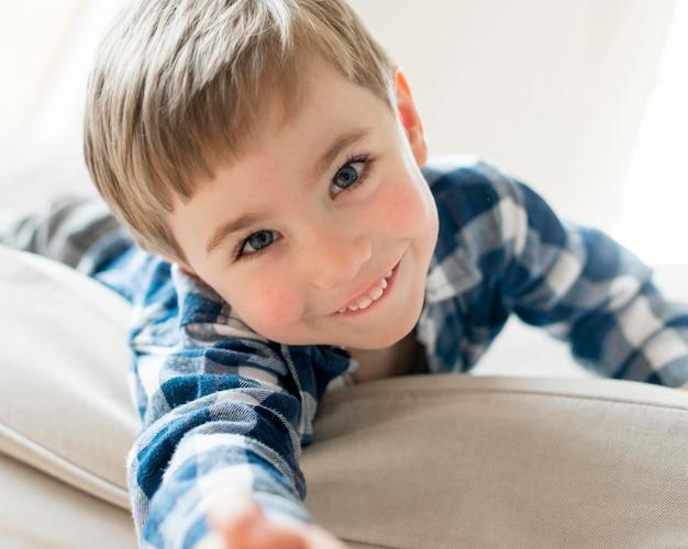 Heureux garçon portant sur le canapé