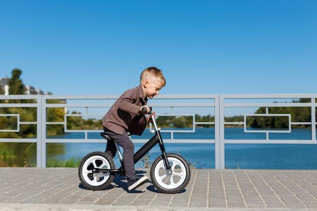 Heureux garçon de quatre ans à vélo sans pédales sur le fond de la rivière et des bâtiments. concept sportif. premier vélo d'équilibre pour petits enfants. une enfance active et amusante à l'extérieur