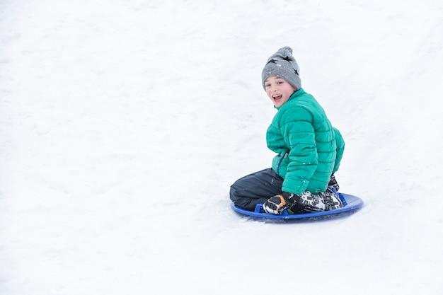 Heureux garçon qui rit glisse en bas de la colline sur une soucoupe à neige. concept saisonnier. jour d'hiver.
