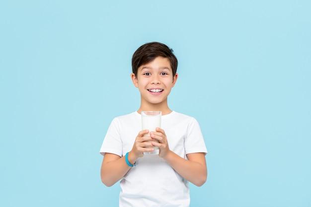 Heureux garçon de race mixte souriant boire du lait frais isolé sur mur bleu clair