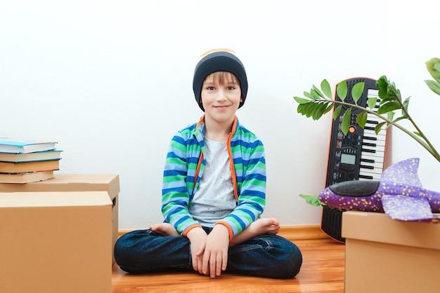 Heureux garçon s'amusant dans le jour du déménagement dans une nouvelle maison. logement d'une jeune famille avec enfant.