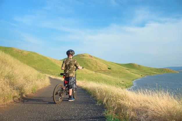 Heureux garçon sur son vélo de montagne sur sentier dans les collines