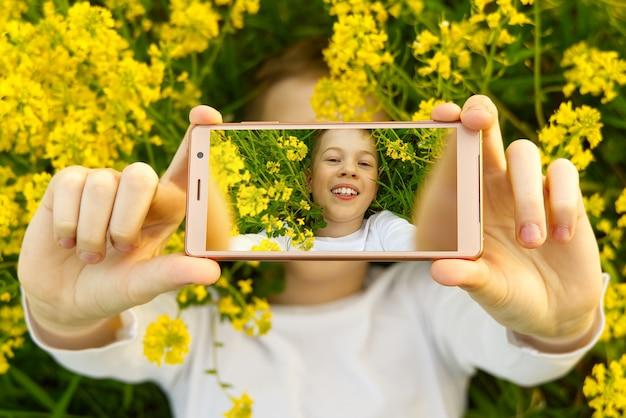 Heureux garçon souriant faisant autoportrait sur smartphone dans la prairie.
