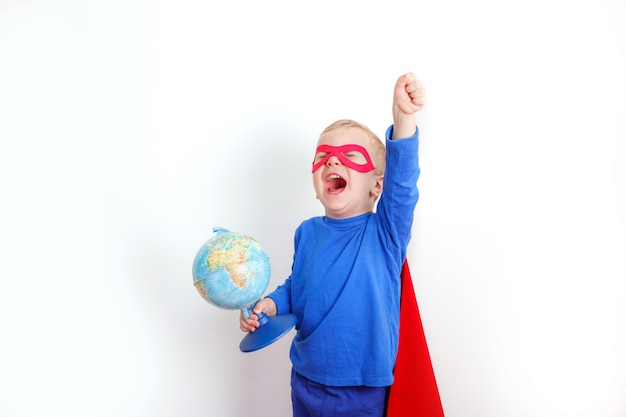 Heureux garçon super héros tenant un globe dans sa main, le concept de sauver le monde