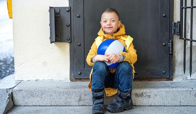 Heureux garçon trisomique avec ballon à l'extérieur assis devant la porte, regardant la caméra.