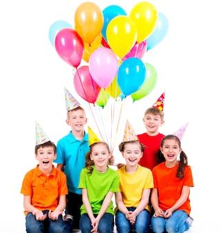 Heureux garçons et filles en chapeau de fête avec des ballons colorés assis sur le sol - isolé sur blanc