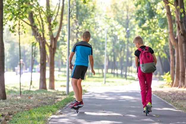 Heureux garçons avec patins à roulettes et scooter dans le parc