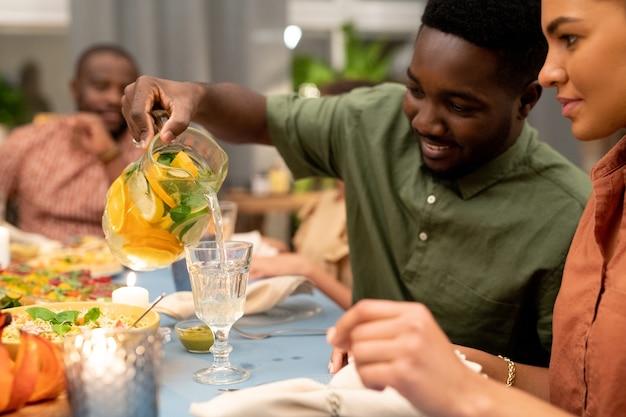 Heureux gars africain versant de la limonade maison fraîche dans le verre de sa sœur ou de sa petite amie par une table de fête servie pendant le dîner de noël