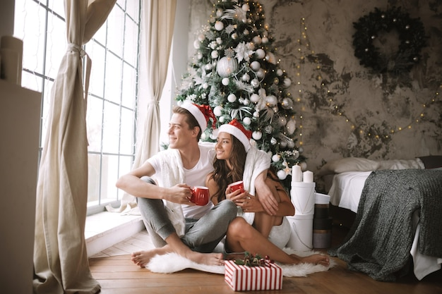 Heureux gars et fille en t-shirts blancs et chapeaux de père noël assis avec des tasses rouges sur le sol devant la fenêtre à côté de l'arbre du nouvel an, des cadeaux et des bougies.